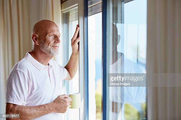 Thoughtful senior man holding cup at home