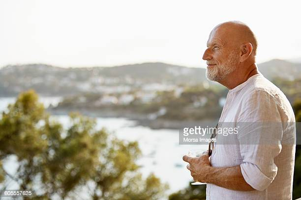 Thoughtful senior man holding wineglass