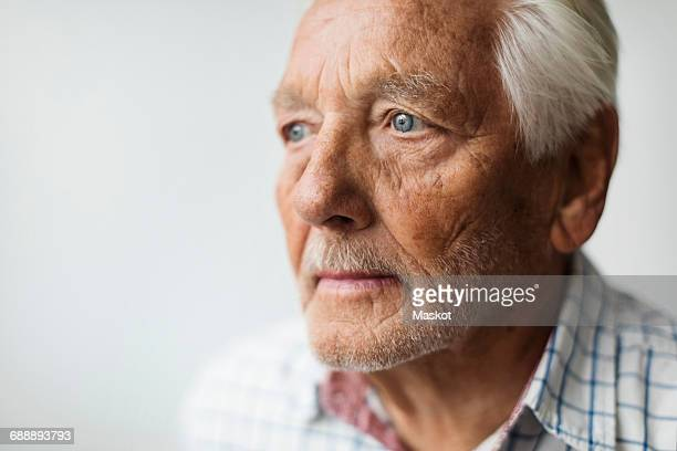 Thoughtful senior man looking away against white background