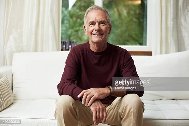 thoughtful senior man looking away on sofa - alleen mannen stockfoto's en -beelden