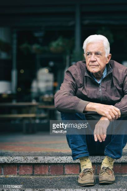 thoughtful senior man looks depressed as he sits in the street - vulnerability stock pictures, royalty-free photos & images