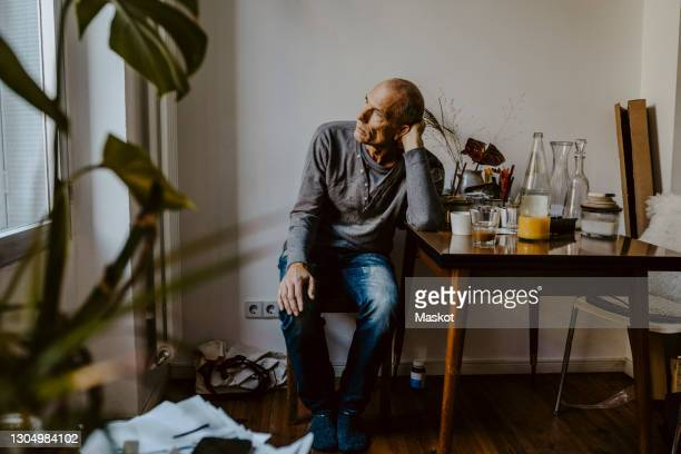 thoughtful senior man sitting on chair in living room - anxiety stock pictures, royalty-free photos & images