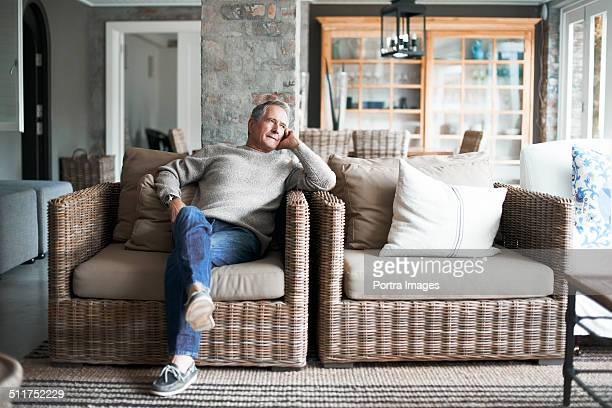 Thoughtful senior man sitting on wicker chair