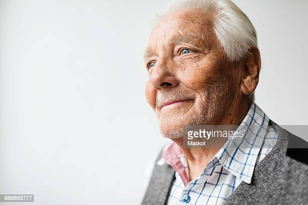 Thoughtful senior man smiling while looking away against white background