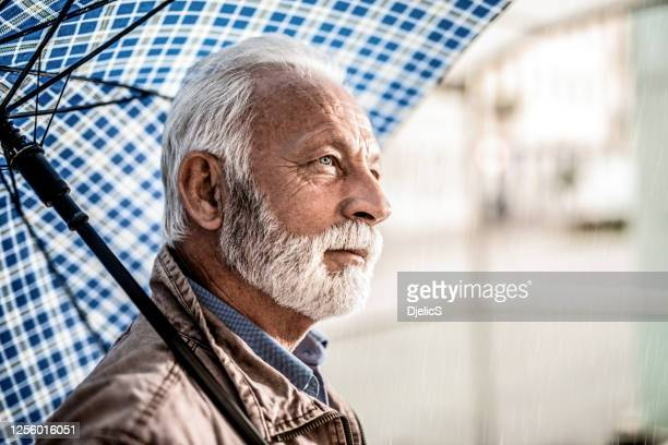 thoughtful senior man waiting under umbrella. - three quarter length stock pictures, royalty-free photos & images