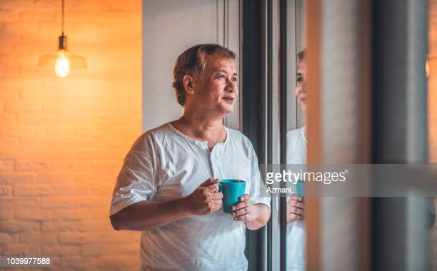 thoughtful senior man with coffee cup by window - one man only stock pictures, royalty-free photos & images