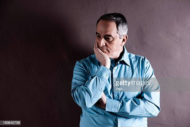 Thoughtful senior wearing blue shirt