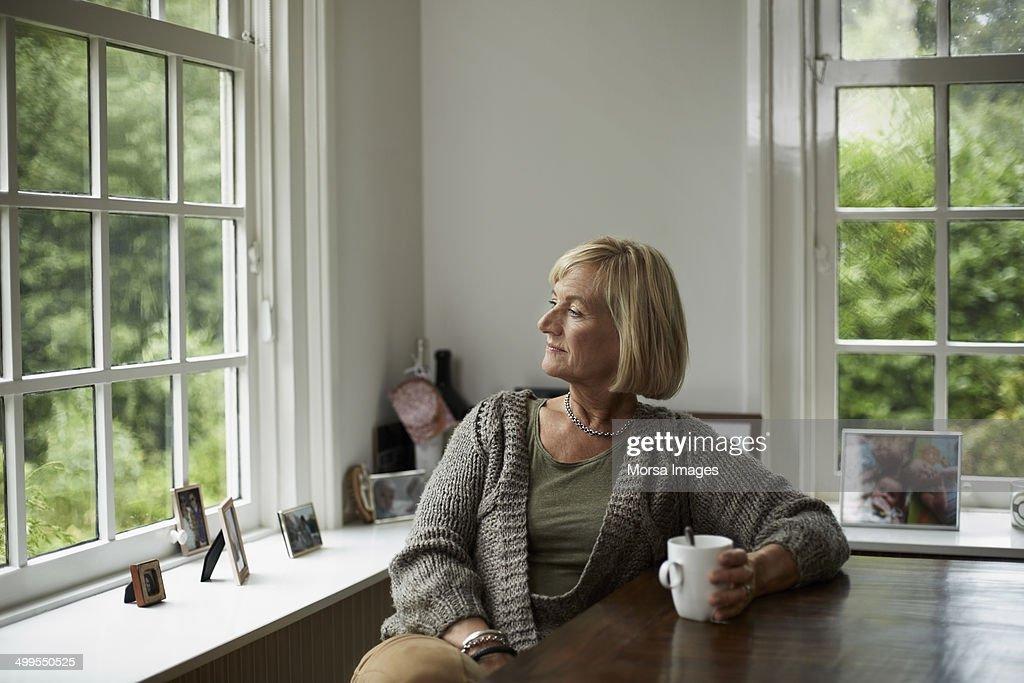 Thoughtful senior woman having coffee : Stockfoto