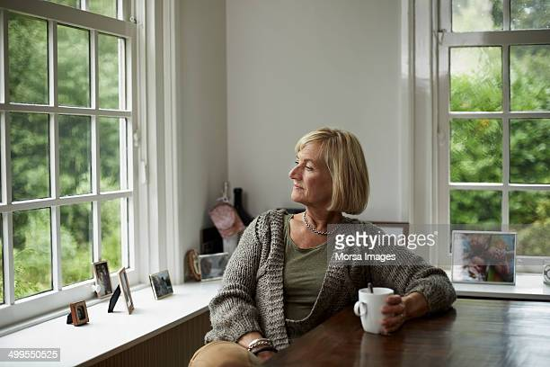 thoughtful senior woman having coffee - 60 anos - fotografias e filmes do acervo