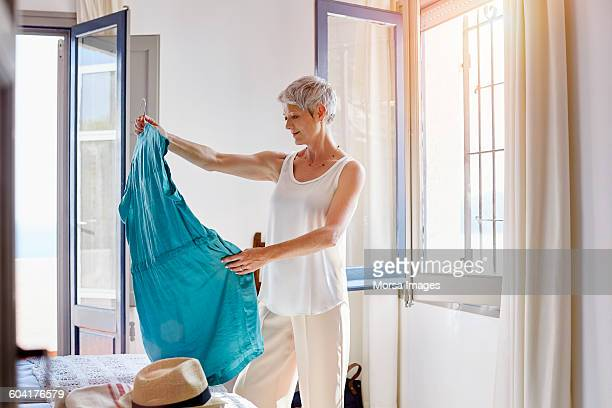 thoughtful senior woman looking at dress - trying on stock pictures, royalty-free photos & images