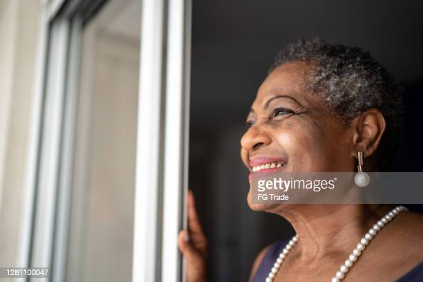 thoughtful senior woman looking at view - positive emotion stock pictures, royalty-free photos & images