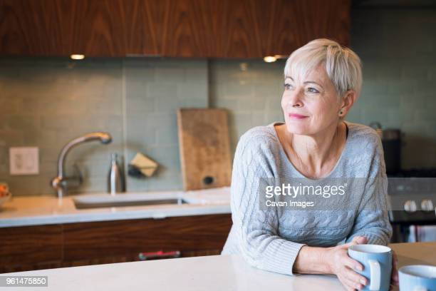 thoughtful senior woman looking away while leaning on table - one senior woman only stock pictures, royalty-free photos & images