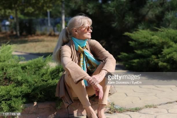 Thoughtful Senior Woman Looking Away While Sitting In Park During Sunny Day