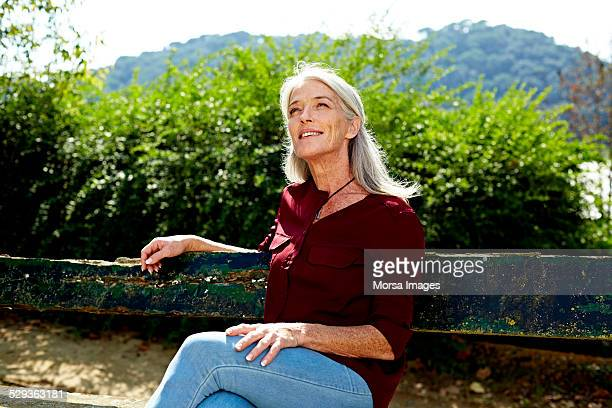 Thoughtful senior woman sitting on park bench