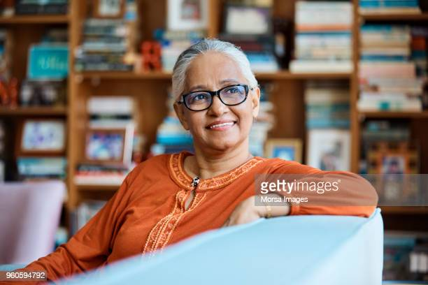 thoughtful senior woman sitting on sofa at home - differential focus stock pictures, royalty-free photos & images