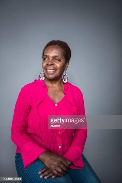 doordachte senior vrouw zitten terwijl u weg - 65 69 jaar stockfoto's en -beelden
