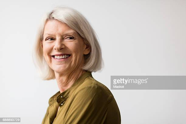 Thoughtful senior woman smiling while looking away against white background