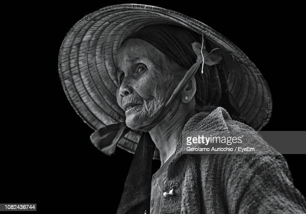 thoughtful senior woman wearing asian style conical hat against black background - chapeau chinois photos et images de collection