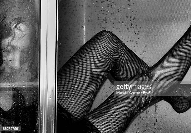 thoughtful sensuous woman lying near window - beautiful legs in stockings stock photos and pictures