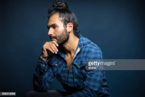 thoughtful serious young man with hand on chin - man bun stock pictures, royalty-free photos & images
