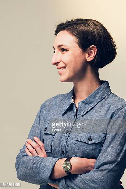 Thoughtful smiling businesswoman against grey wall