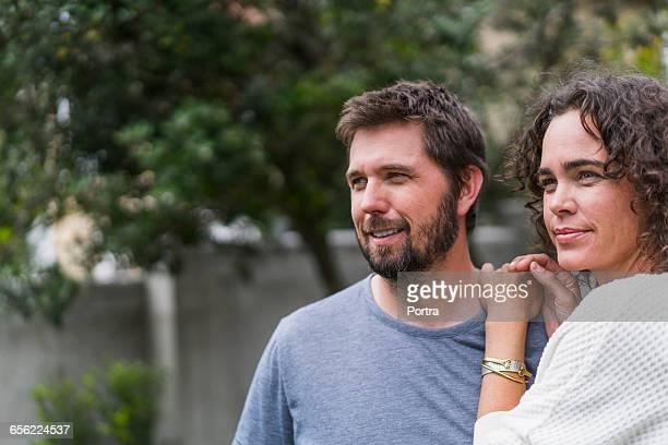 thoughtful smiling couple standing in back yard - homens de idade mediana - fotografias e filmes do acervo