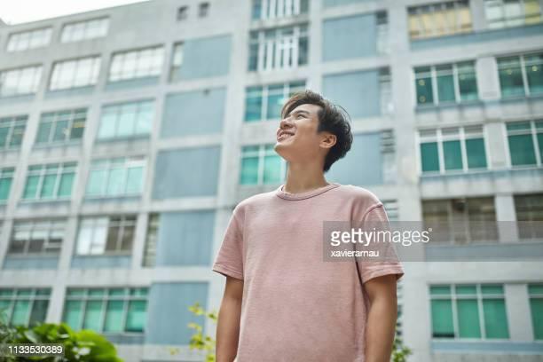 都会の建物に対して思いやりのある笑顔の男 - ローアングル ストックフォトと画像