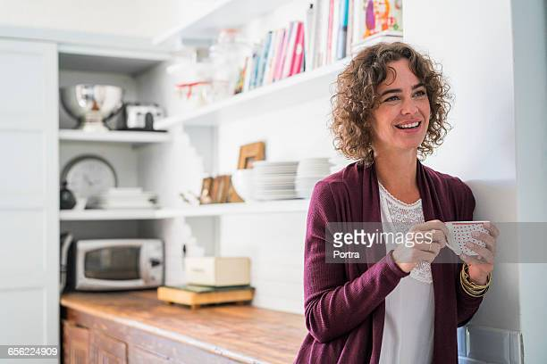 Thoughtful smiling woman holding coffee cup