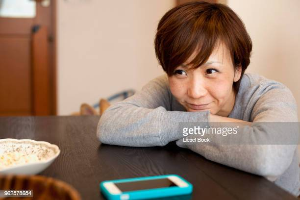 Thoughtful smiling woman leaning on table with arms crossed at home