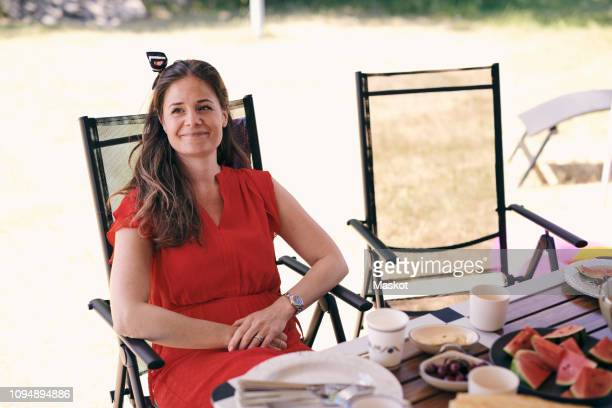 thoughtful smiling woman sitting at table on folding chair at campsite - cadeira dobrável - fotografias e filmes do acervo