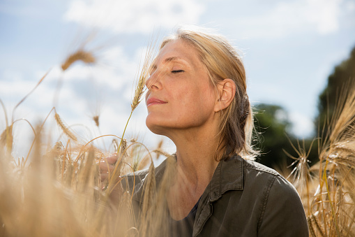 Thoughtful smiling woman with closed eyes resting amidst crops at farm on sunny day - gettyimageskorea