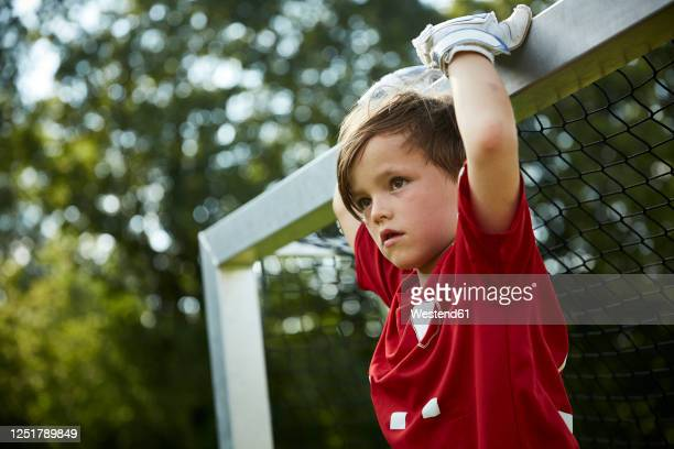 thoughtful soccer boy holding goal post at field - torpfosten stock-fotos und bilder