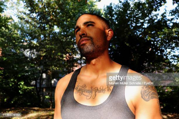 Thoughtful Tattooed Man Looking Away In Park