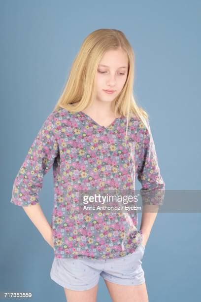 Thoughtful Teenage Girl Standing With Hands In Pockets Against Blue Background