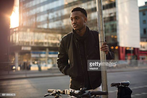 thoughtful teenager standing by pole against buildings in city - looking away stock pictures, royalty-free photos & images