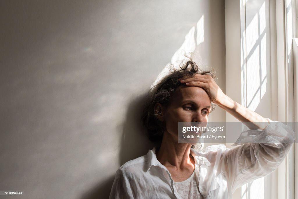 Thoughtful Tensed Woman Against Wall By Window At Home : Stock Photo