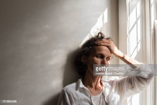 thoughtful tensed woman against wall by window at home - depression stock-fotos und bilder
