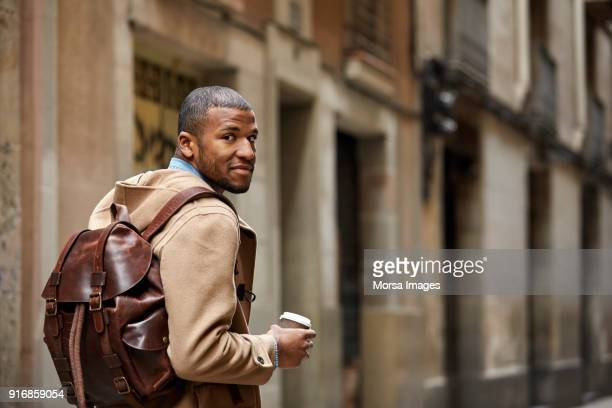 thoughtful tourist with coffee cup against wall - brown coat stock pictures, royalty-free photos & images