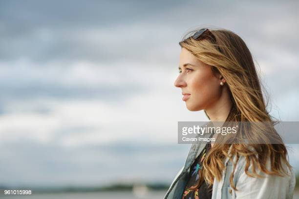 thoughtful woman against sky - mid length hair stock pictures, royalty-free photos & images
