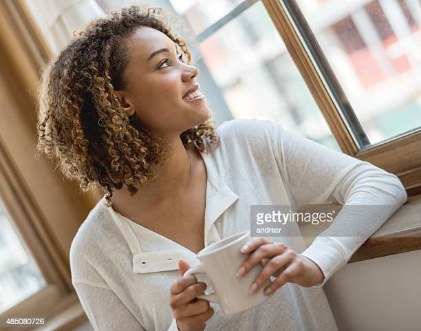 Thoughtful woman at home drinking coffee