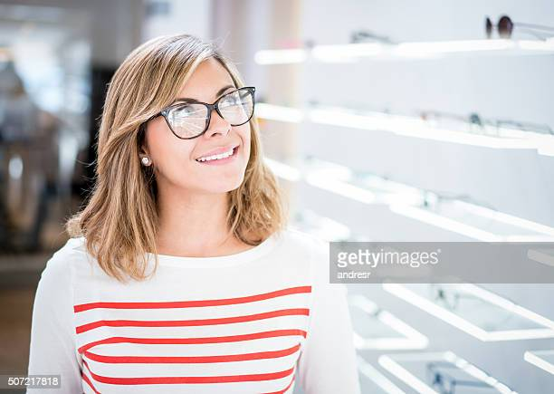 Thoughtful woman at the optician trying glasses