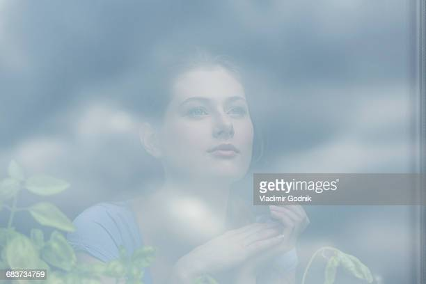thoughtful woman by potted plants seen through glass window - photographed through window stock pictures, royalty-free photos & images