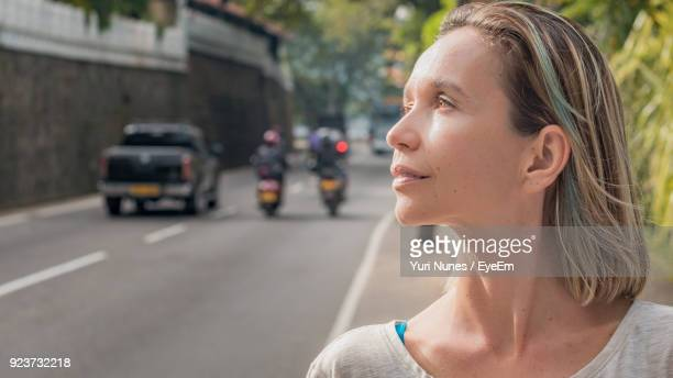 thoughtful woman by road - kandy kandy district sri lanka stock photos and pictures