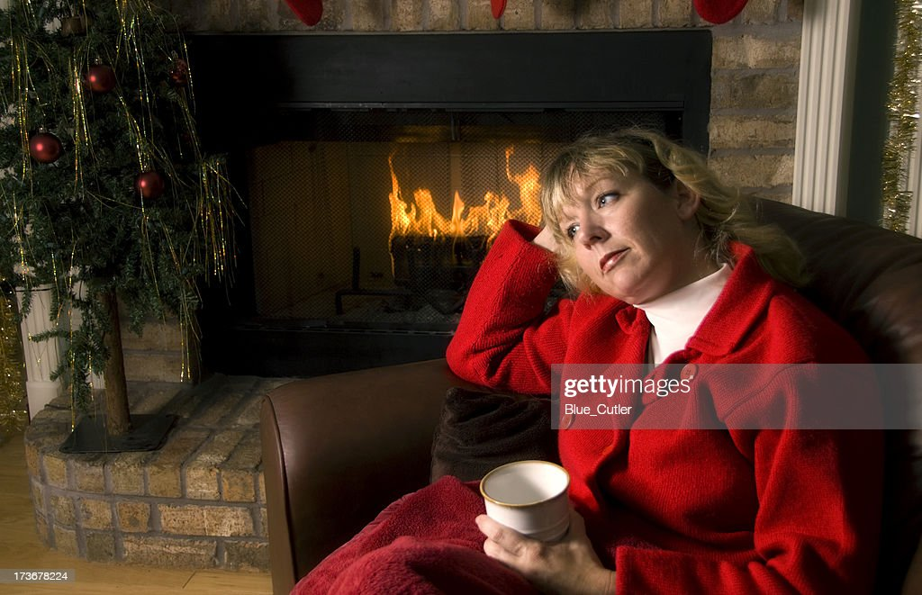 Thoughtful woman by the Fireplace at Christmas : Stock Photo