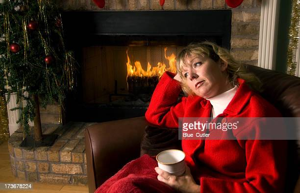 Thoughtful woman by the Fireplace at Christmas