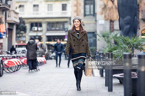 thoughtful woman carrying shopping bags in city - bollard stock photos and pictures