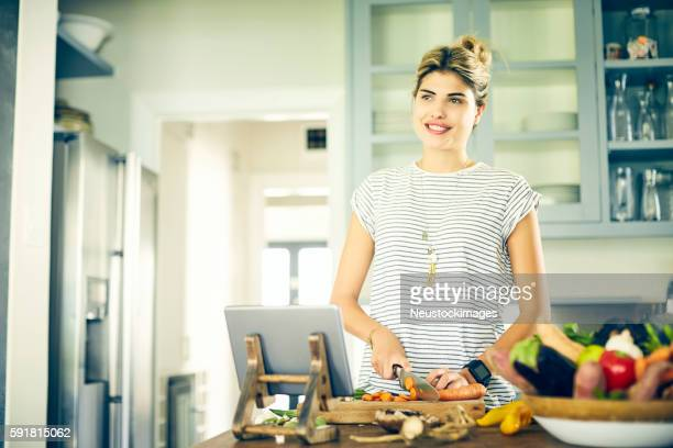 Thoughtful woman cutting carrot while using digital tablet
