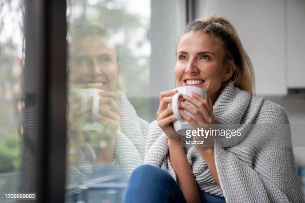 mulher pensativa bebendo uma xícara de café em casa - inverno - fotografias e filmes do acervo