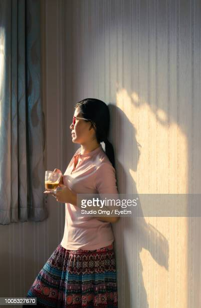 Thoughtful Woman Drinking Coffee While Standing By Wall At Home