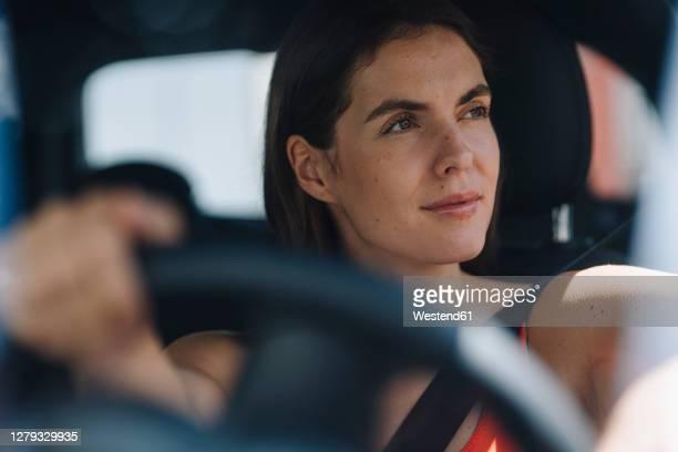 thoughtful woman driving car - conduzir imagens e fotografias de stock